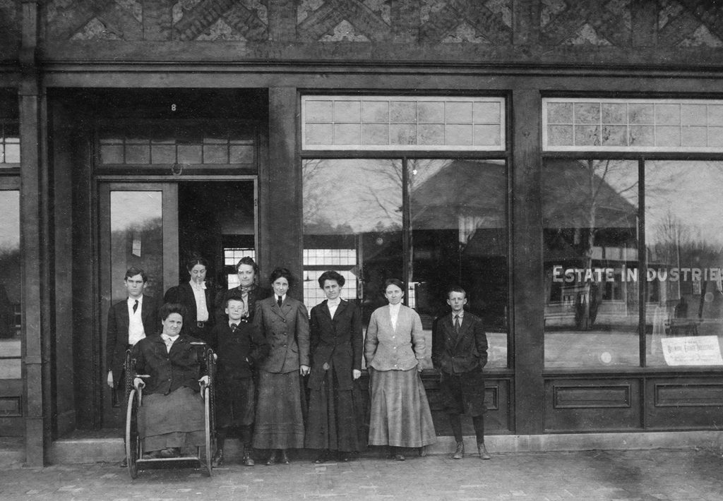 Archival photo (circa 1905) of the facade of Biltmore Estate Industries in Asheville, NC. Standing in the doorway, left to right, Charlotte Louise Yale and Eleanor Park Vance.