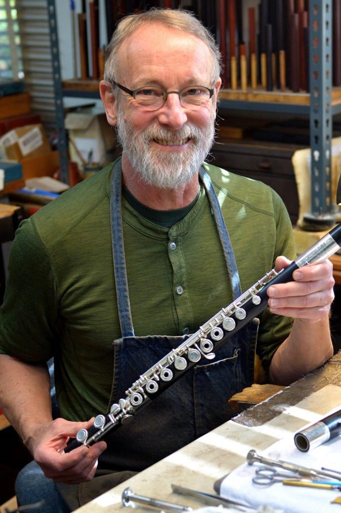 Flutemaker Chris Abell holding a wooden flute in his Grovewood Village studio.