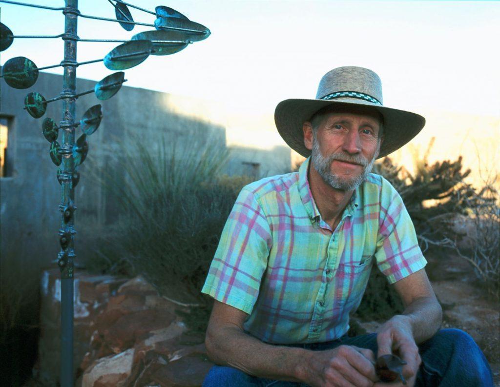 Utah artist Lyman Whitaker posing in front of his Wind Sculpture.