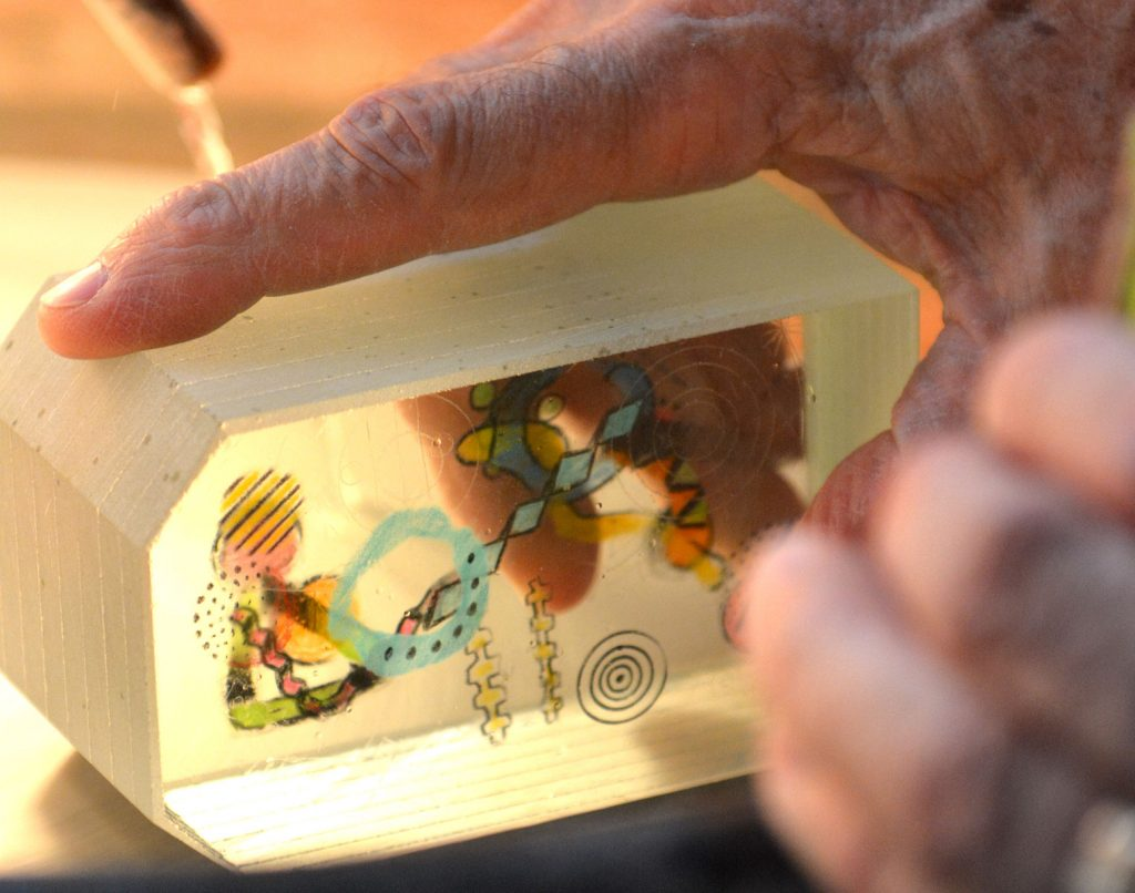 Close-up of Carl Powell's hands working on a glass sculpture in his Grovewood Village studio.