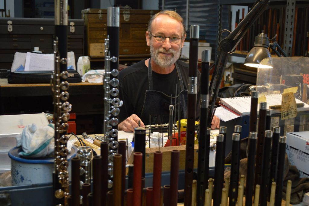 Wooden flutemaker Chris Abell posing behind some flutes in his studio at Grovewood Village in Asheville.