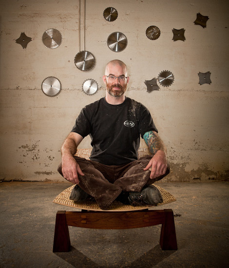 Furniture maker Robb Helmkamp sitting on one of his handcrafted chairs in his studio.