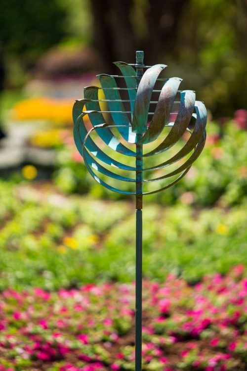 Nautilus wind sculpture in a garden environment.