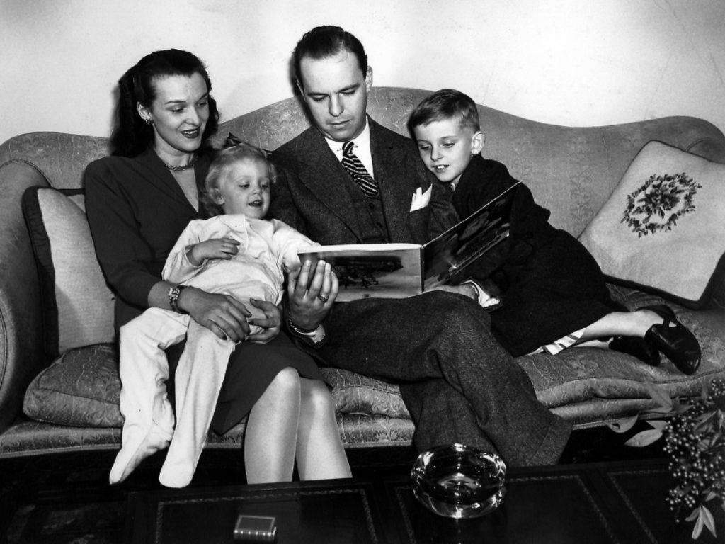 Fred Loring Seely and his wife, Evelyn Grove Seely, reading a story to their two children.