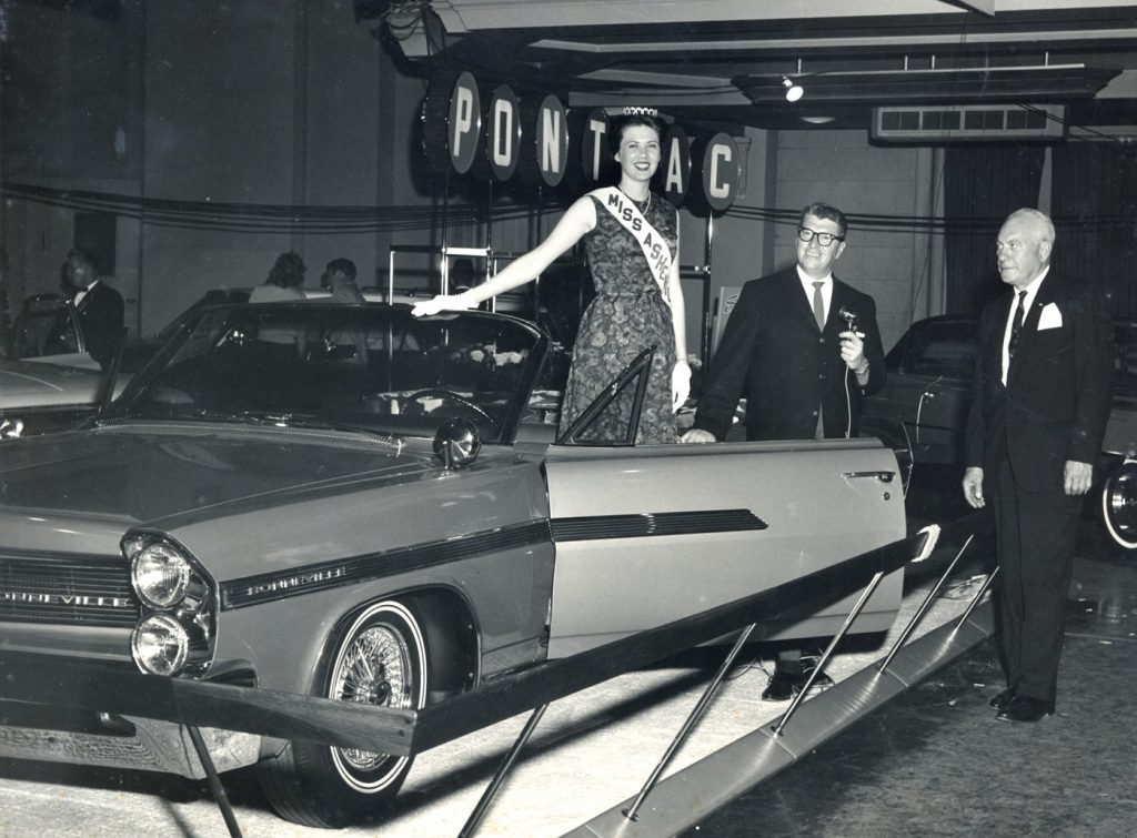 Miss Asheville and Harry Blomberg (far right) at a car show in downtown Asheville circa 1962.