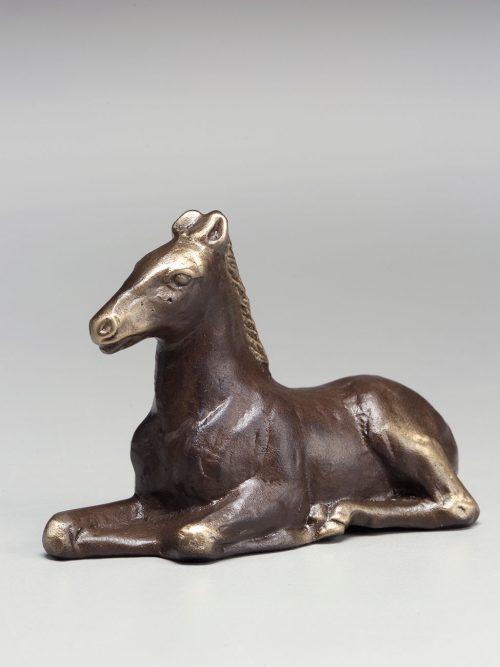 Reclining bronze pony sculpture by artist Scott Nelles.