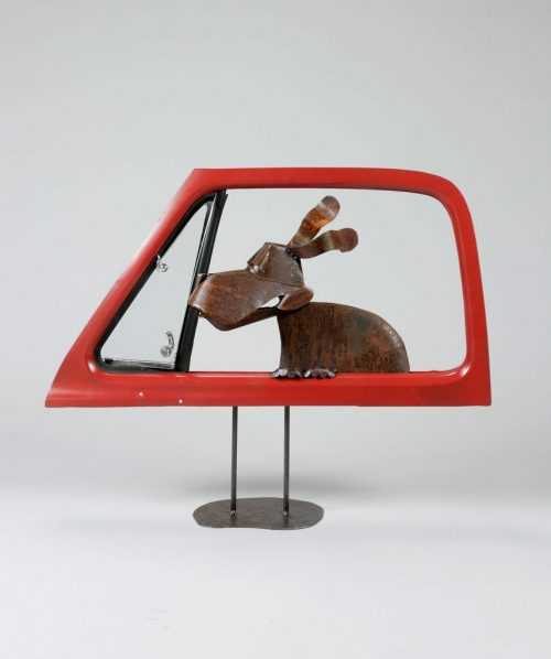 Metal outdoor sculpture of a dog in a car window by Asheville artist Dave Taylor.