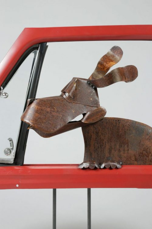 Detail of dog in car window metal yard sculpture by Dave Taylor.