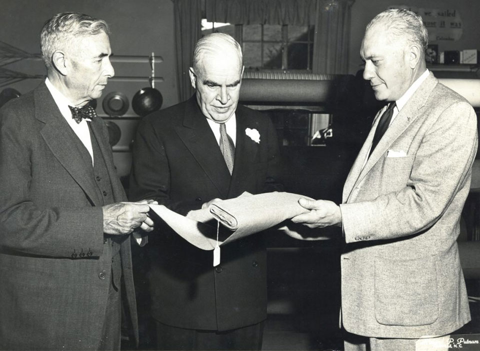 Harry Blomberg presents a bolt of Biltmore Homespun to North Carolina Governor Luther H. Hodges, circa 1953.