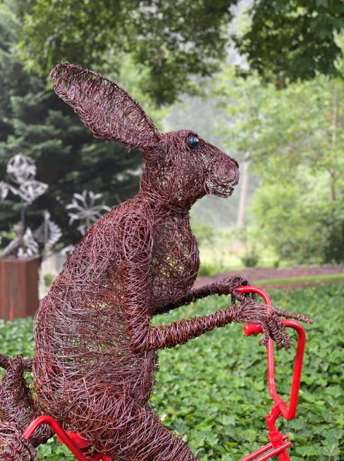 A sculpture by Josh Cote of two rabbits made of wire riding a tandem bike.