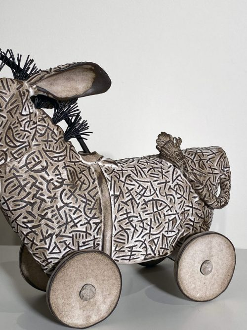 Kiln-fired ceramic sculpture by Libba Tracy of a donkey chasing a carrot.
