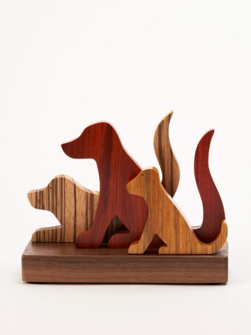 Wooden sculpture of 3 dogs by artist Jerry Krider.