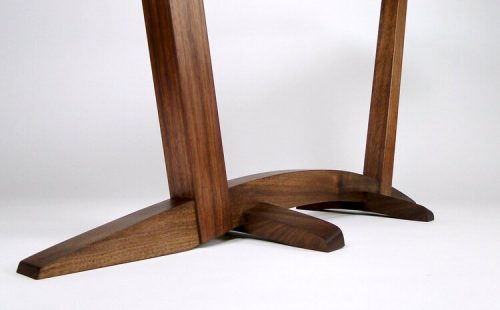Details of a walnut base of a console table.