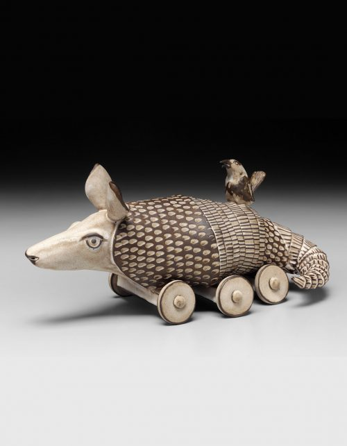 Fine art ceramic sculpture by Libba Tracy of a Carolina wren perched on the back of an armadillo.