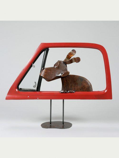 Metal dog in a car door sculpture by Asheville artist Dave Taylor.