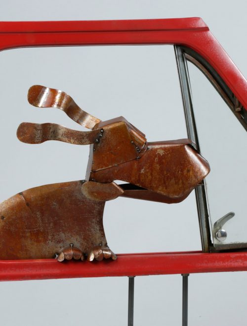 Detail of a metal dog in car door sculpture by Asheville artist Dave Taylor.
