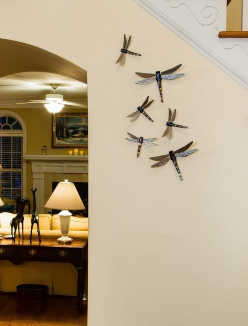 Display of dragonfly wall art by John Running in a home.
