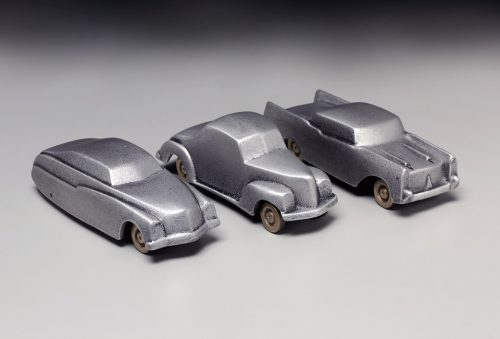 A grouping of three retro car sculptures by Scott Nelles.