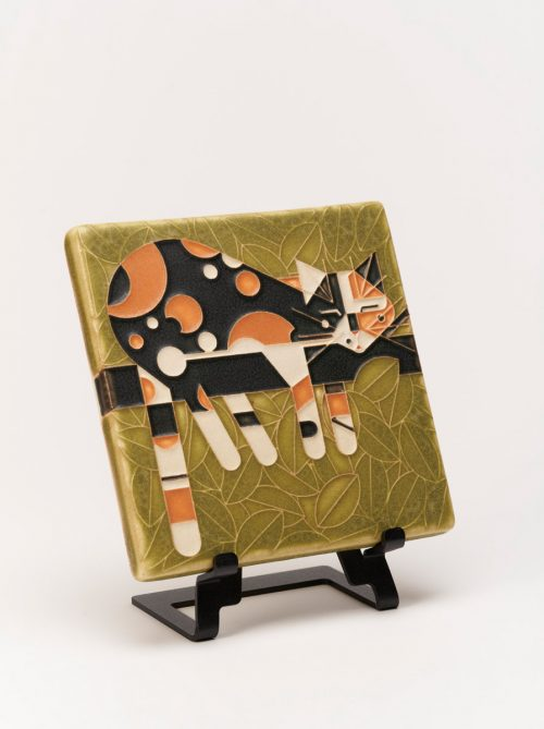 A ceramic art tile of a cat lying on a limb by Motawi Tileworks.