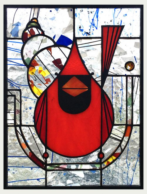 A stained glass window panel by Jacob Hinnenkamp featuring a Charley Harper cardinal design.